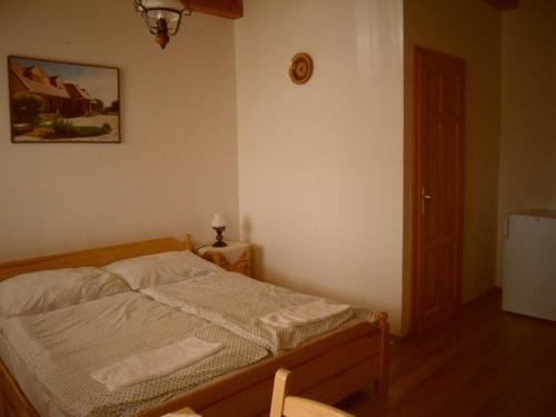A bed or beds in a room at Nosztalgia Vendégház