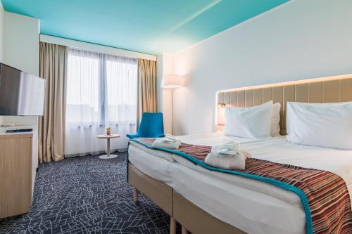 Кровать или кровати в номере Park Inn by Radisson Pribaltiyskaya Hotel and Congress Centre