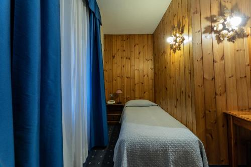 A bed or beds in a room at Hotel Courmayeur