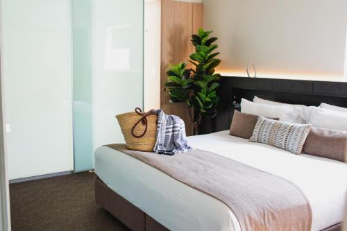 A bed or beds in a room at Seahaven Noosa Beachfront Resort