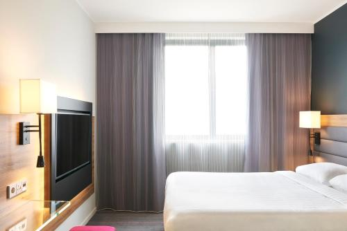 A bed or beds in a room at Moxy Milan Malpensa Airport