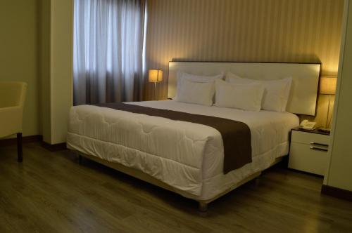 A bed or beds in a room at Limaq Hotel
