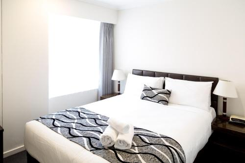 A bed or beds in a room at Seasons Darling Harbour