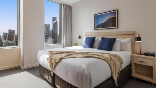 A bed or beds in a room at Oaks Melbourne on Market Hotel