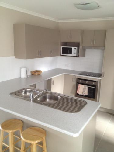 A kitchen or kitchenette at Denman Serviced Apartments