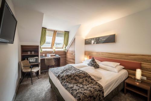A bed or beds in a room at BEST WESTERN Plus Hotel Goldener Adler Innsbruck