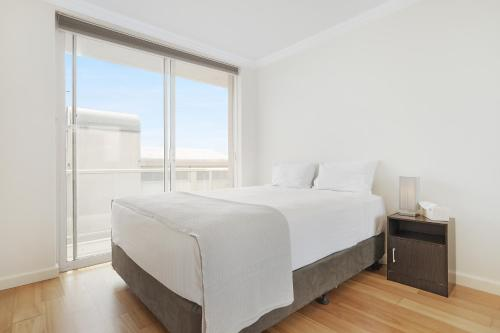 A bed or beds in a room at Modern beach pad, panoramic rooftop water views