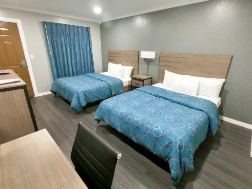 A bed or beds in a room at Budget Host Inn