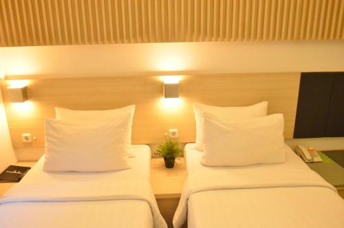 A bed or beds in a room at Malaka Hotel Bandung