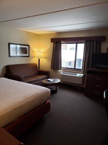 A bed or beds in a room at AmericInn by Wyndham Iron River