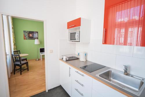 A kitchen or kitchenette at ActiLingua Apartment Hotel
