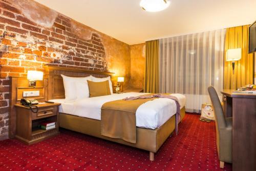 A bed or beds in a room at Romantik Hotel Scheelehof Stralsund