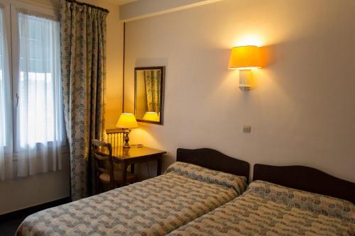 A bed or beds in a room at Hôtel de Flandre