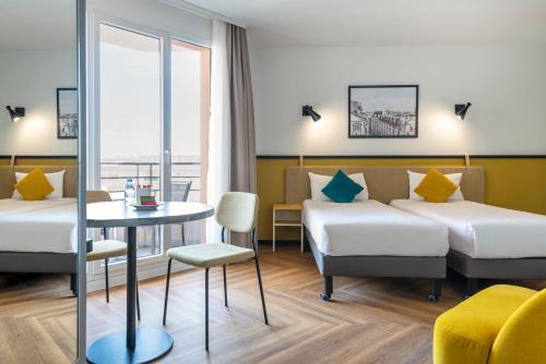 Кровать или кровати в номере Aparthotel Adagio Paris Montrouge