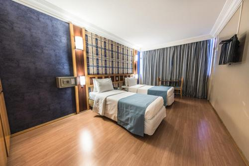 A bed or beds in a room at Monumental Bittar Hotel