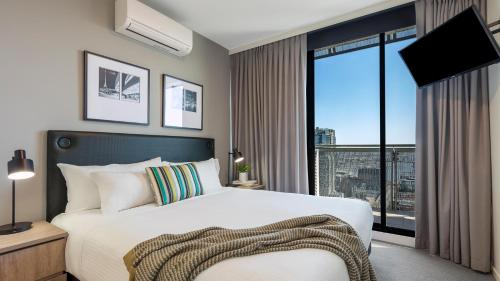 A bed or beds in a room at Oaks Melbourne on William Suites