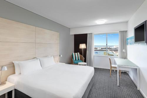 A bed or beds in a room at Vibe Hotel Darwin Waterfront