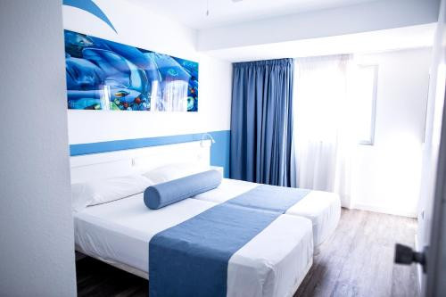 A bed or beds in a room at Corralejo Surfing Colors Hotel&Apartments