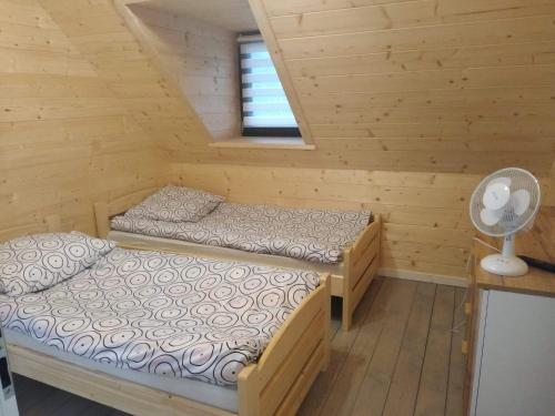A bed or beds in a room at Domek u Weroniki
