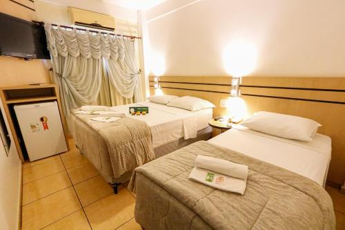 A bed or beds in a room at Hotel Villa Quati