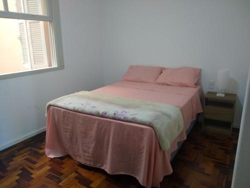 A bed or beds in a room at Quarto aconchegante no Calçadão