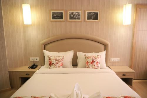 A bed or beds in a room at Hotel Mayvilas, Luxury Boutique Stays
