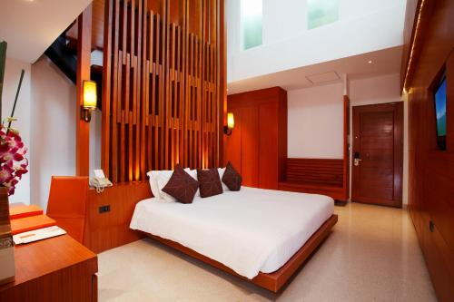 A bed or beds in a room at La Flora Resort Patong