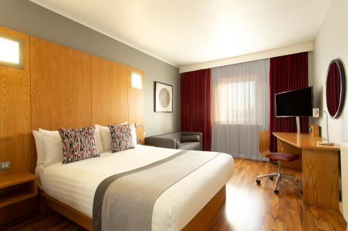 A bed or beds in a room at Ramada by Wyndham Belfast