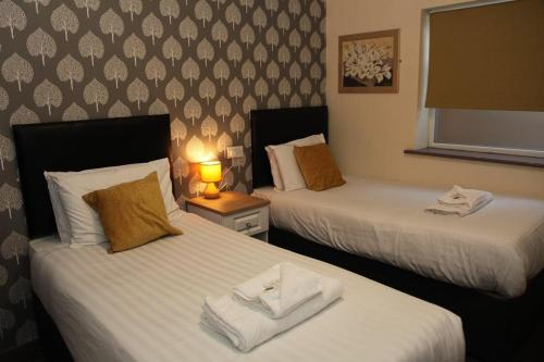 A bed or beds in a room at Minworth Lodge