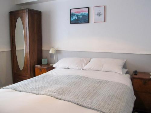 A bed or beds in a room at Stone's Throw Guest House