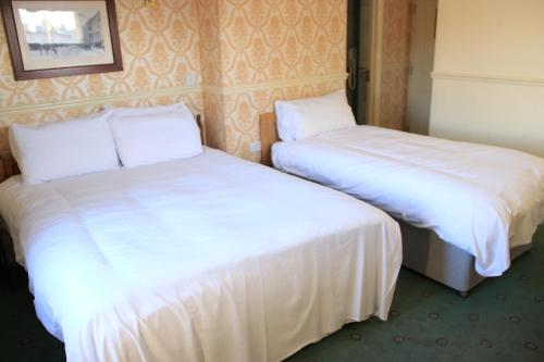 A bed or beds in a room at Station Hotel – RelaxInnz