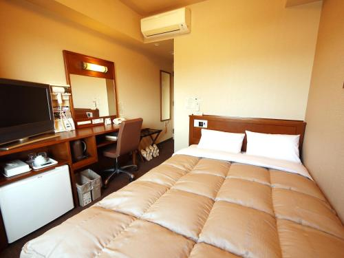 A bed or beds in a room at Hotel Route-Inn Gotenba Eki-Minami