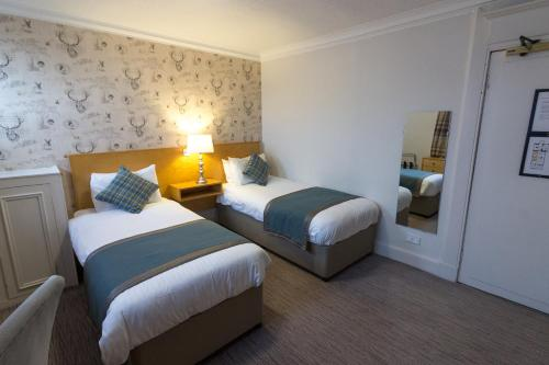 A bed or beds in a room at Tullie Inn
