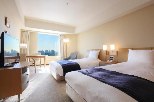 A bed or beds in a room at Tokyo Dome Hotel