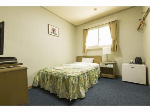 A bed or beds in a room at Takamado