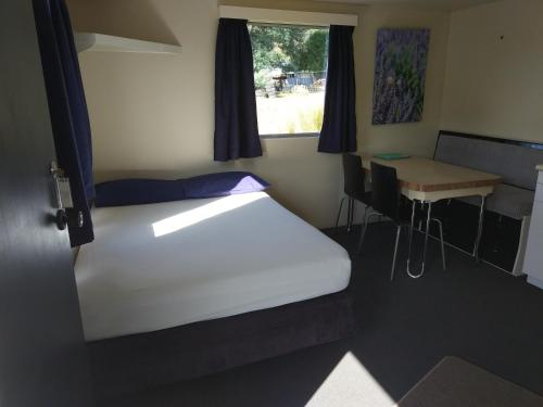 A bed or beds in a room at Picton's Waikawa Bay Holiday Park
