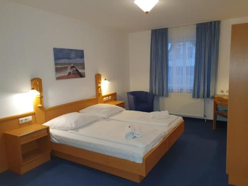 A bed or beds in a room at Hotel-Pension Pastow Garni
