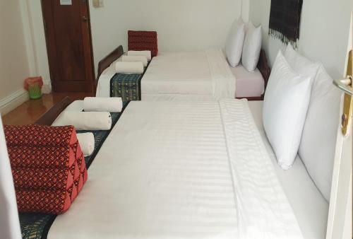 A bed or beds in a room at Smiley's Guesthouse