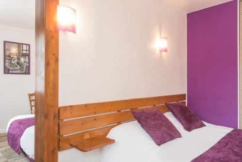A bed or beds in a room at Hôtel du Moulin de la Brevette