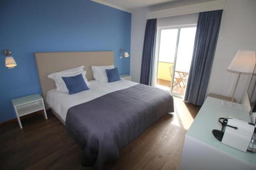 Кровать или кровати в номере Vinha da Areia Beach Hotel