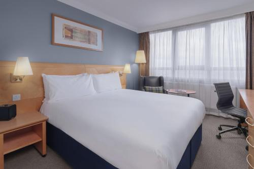 A bed or beds in a room at Holiday Inn London Kensington Forum