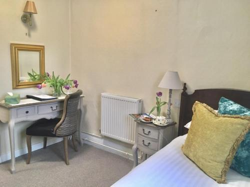 A bed or beds in a room at Drayton Court Hotel