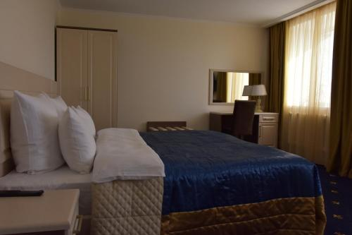 A bed or beds in a room at Dostyk Hotel