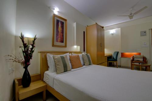 A bed or beds in a room at Tristar Service Apartments