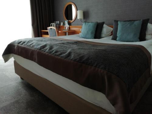 A bed or beds in a room at Ramada Resort Kranjska Gora