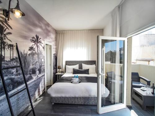 A bed or beds in a room at Dizengoff Avenue Boutique Hotel