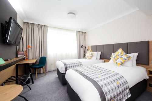 A bed or beds in a room at Holiday Inn London - Gatwick Airport