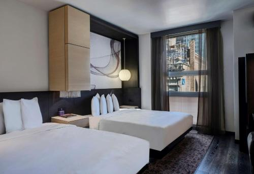A bed or beds in a room at Hyatt Herald Square New York