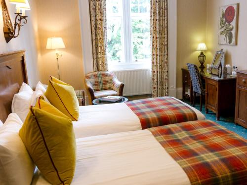 A bed or beds in a room at Pine Trees Hotel Pitlochry