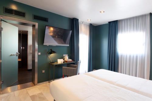 Petit Palace Puerta de Triana tesisinde bir odada yatak veya yataklar